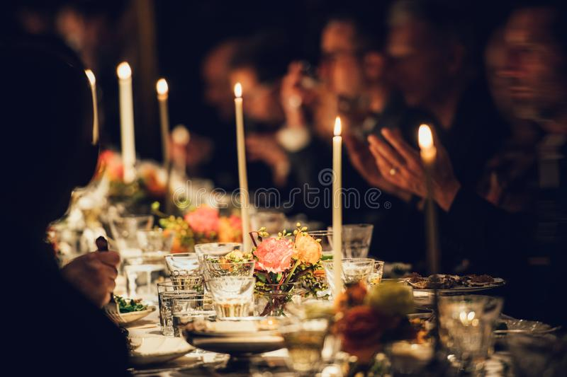 People enjoy a family dinner with candles. Big table served with food and beverages royalty free stock images