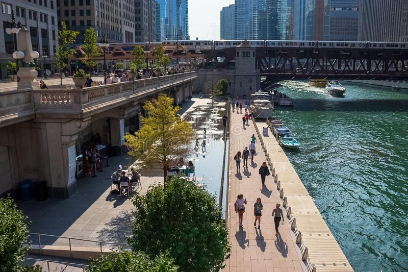 People enjoy summer in Chicago on riverwalk, splash pad, boat, Wacker Dr., and el trail over Chicago River. Chicago, IL / USA - 7/23/19:  People enjoy summer in royalty free stock photography