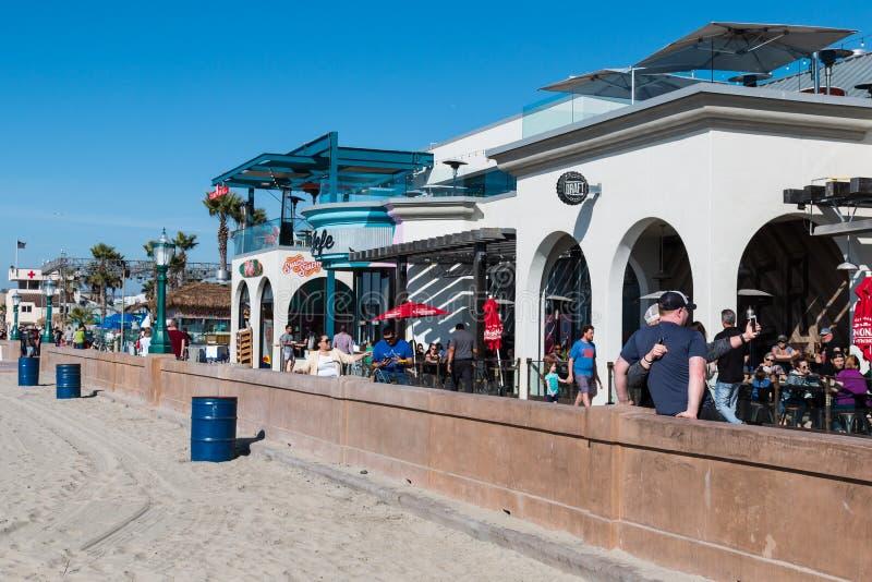 People Enjoy a Sunny Day of Mission Beach Boardwalk in San Diego. SAN DIEGO, CALIFORNIA - FEBRUARY 9, 2018: People enjoy a sunny day at the shops and restaurants royalty free stock image