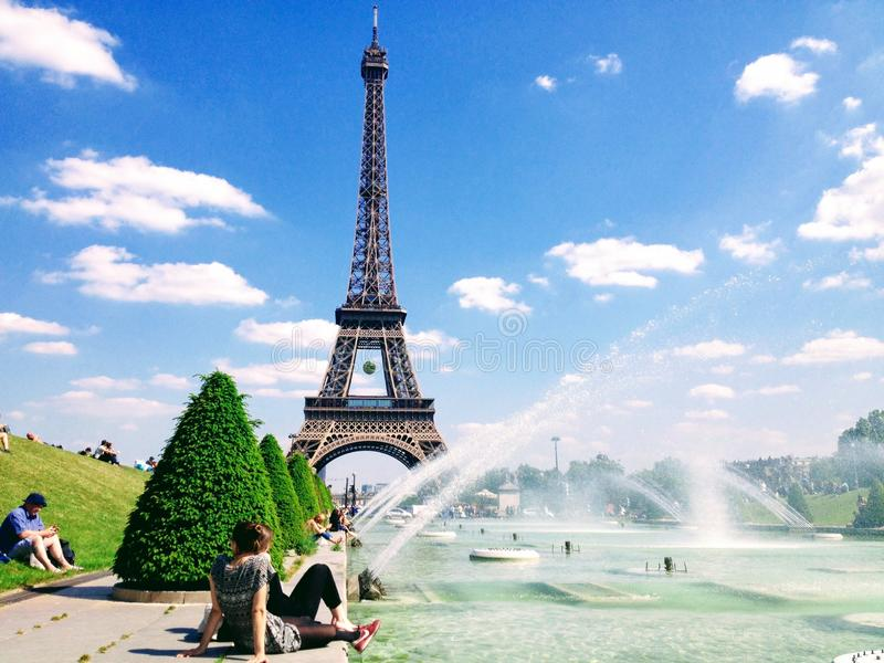 People enjoy sunshine and fountain pool in front of the Eiffel Tower stock images
