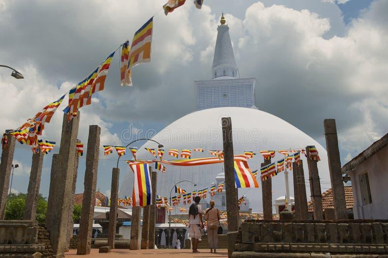 People enjoy the view to the Ruwanwelisaya stupa in Anuradhapura, Sri Lanka. ANURADHAPURA, SRI LANKA - MAY 19, 2011: Unidentified people enjoy the view to the royalty free stock photo