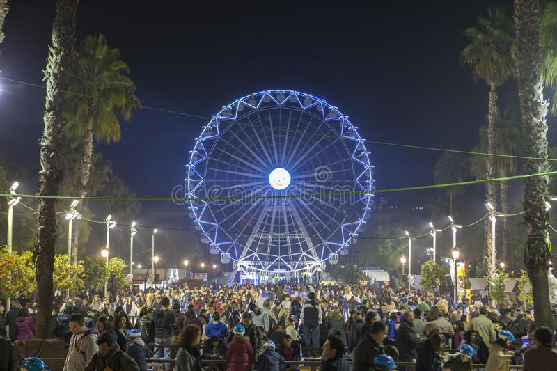 People enjoy visiting Christmas market with ferris wheel and ice. Seville, Spain - January 3, 2017: People enjoy visiting Christmas market with ferris wheel and stock photos