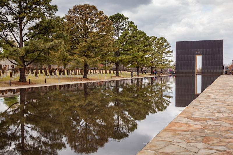 People Enjoy Visiting OKC Bombing Memorial. OKLAHOMA CITY, OKLAHOMA / USA - MARCH 31, 2018: People walking around and visiting the OKC Bombing Memorial and stock photography