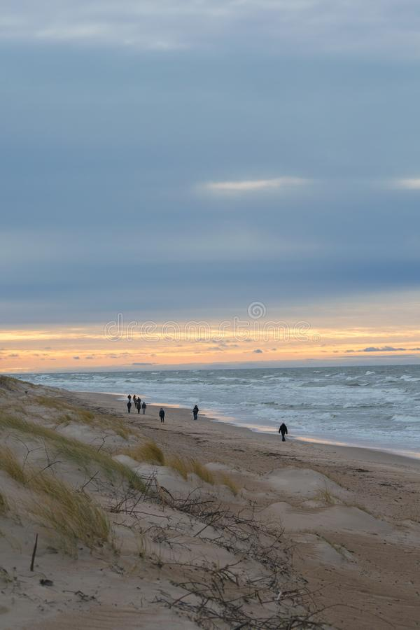 People walking on beach in winter evening in Palanga royalty free stock photography