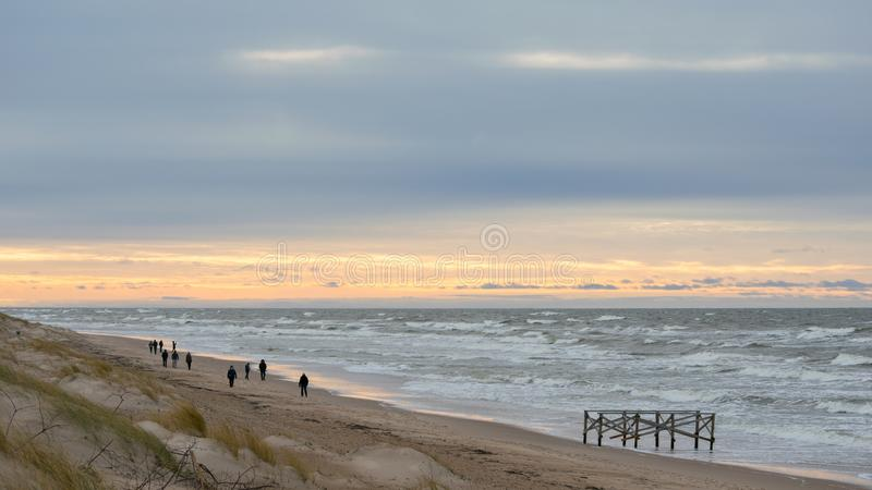 People walking on beach in winter evening in Palanga royalty free stock image