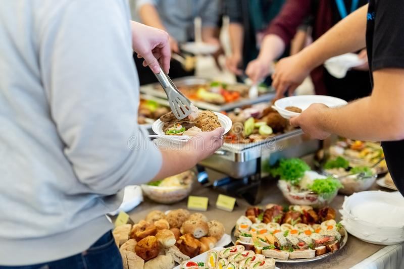People enjoying buffet meal. Close up of people serving themselves with canapes in buffet of restaurant stock photography