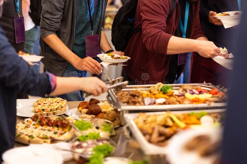 People enjoying buffet meal. Close up of people serving themselves with canapes in buffet of restaurant royalty free stock photo