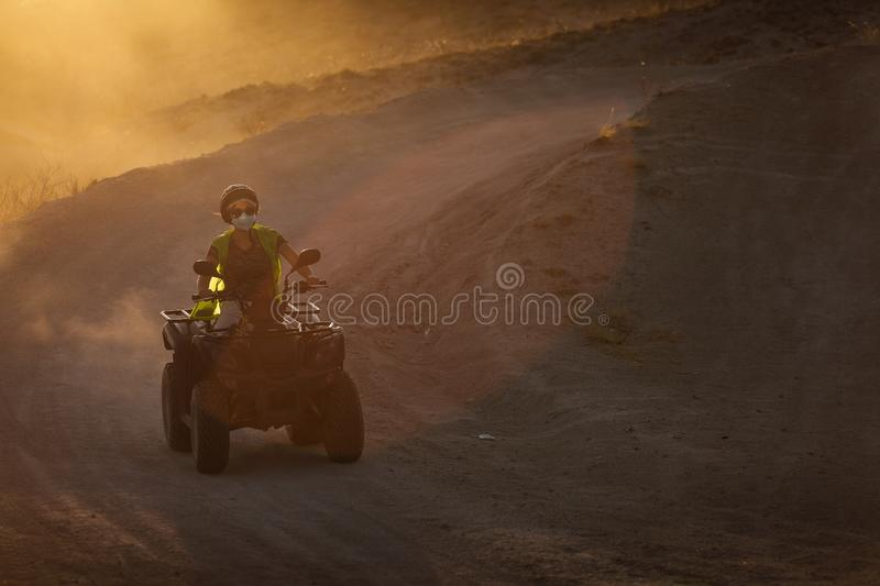 People enjoying driving atv on sunset in Valleys of Cappadocia with lot of dusts in background.  royalty free stock photos