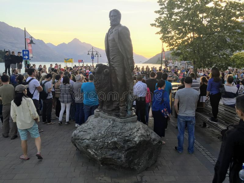 People enjoying an evening street performance on the Main Town Pier in beautiful Queenstown. Queenstown, South Island, New Zealand - February 7th, 2016: People stock photos