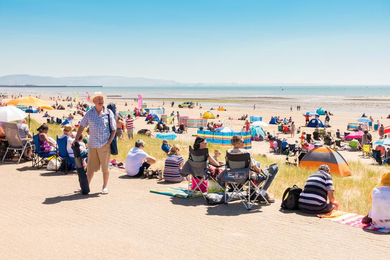 People Enjoying Hot Summer Day on the Beach. Swansea, United Kingdom - June 30, 2018: People are enjoying a hot sunny summer day at the public beach in Swansea stock photos
