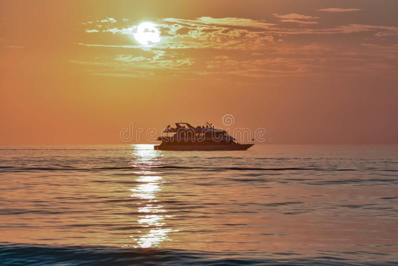 People enjoying luxury yacht on colorful sunset background in Gulf Coast Beaches. stock photo