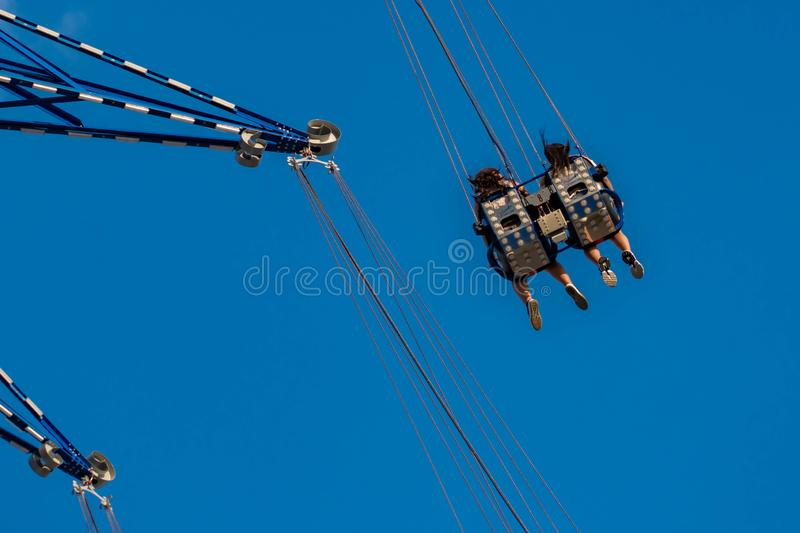 """People enjoying Orlando Star Flyer. It is the """"world's tallest swing ride standing at 450 feet.  in International Drive area. Orlando, Florida. May stock photo"""