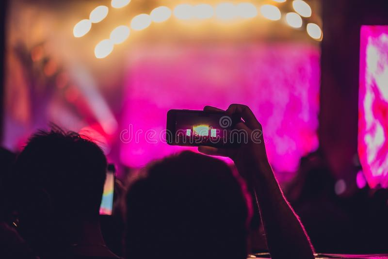 People enjoying rock concert and taking photos with cell phone at music festival.  royalty free stock photos