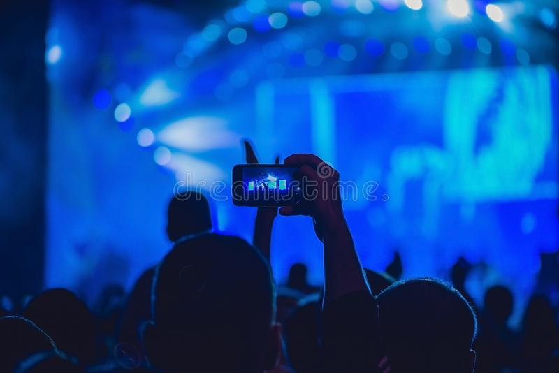 People enjoying rock concert and taking photos with cell phone at music festival.  royalty free stock photography