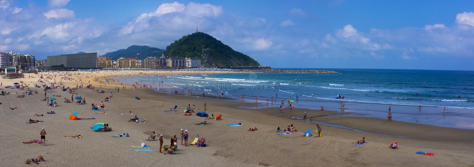 People enjoying the sun on Zurriola beach, City of San Sebastian, Basque Country stock image