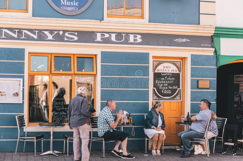 People enjoying a sunny day in the pubs in Dingle, small port town on the southwest of Ireland Dingle Peninsula royalty free stock photos