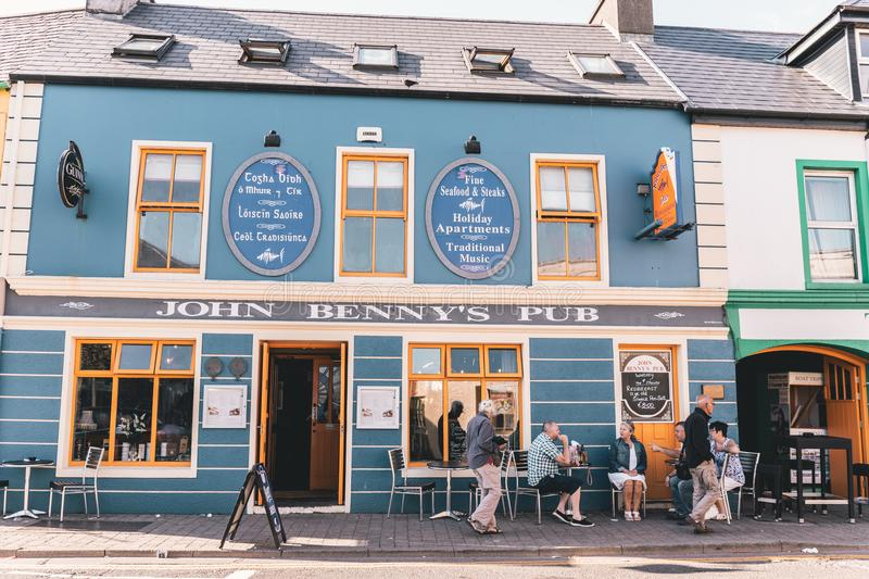 People enjoying a sunny day in the pubs in Dingle, small port town on the southwest of Ireland Dingle Peninsula. June 4th, 2018, Dingle, Ireland - small port royalty free stock image