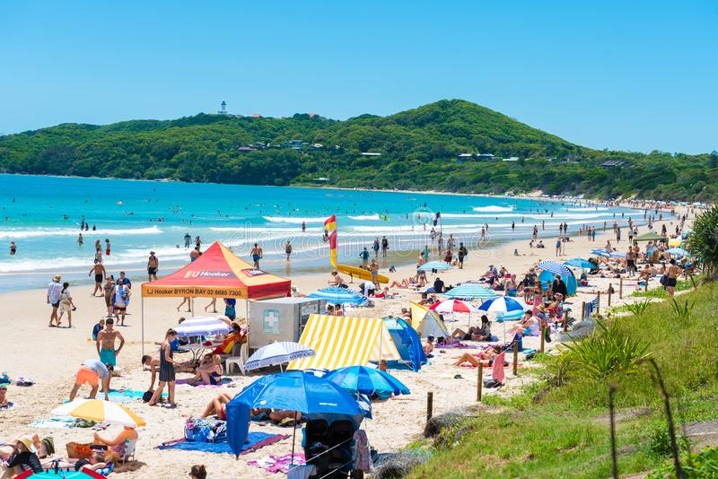 People enjoying the sunny weather on the beach at Byron Bay, NSW, Australia. Byron Bay, NSW, Australia- January 3, 2018: People enjoying the sunny weather on the royalty free stock image