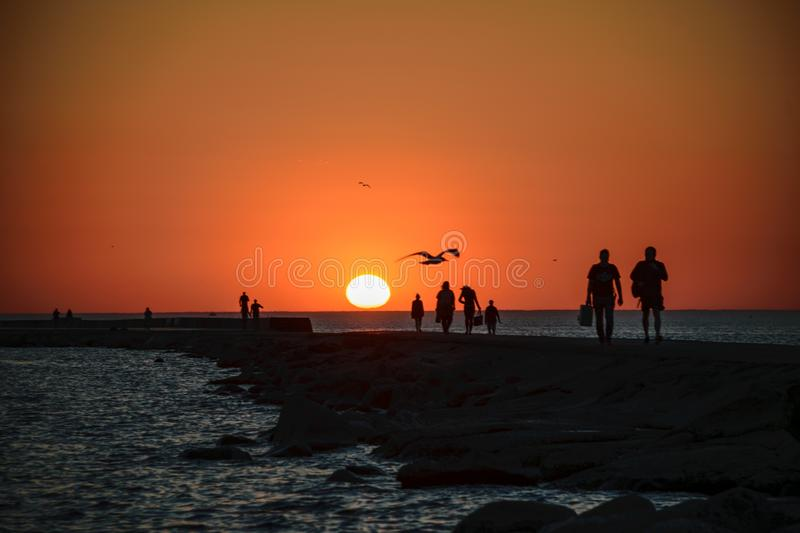 people enjoying sunset on the brakewater in the sea royalty free stock photos