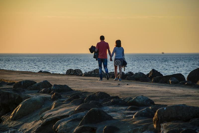 people enjoying sunset on the brakewater in the sea stock photo
