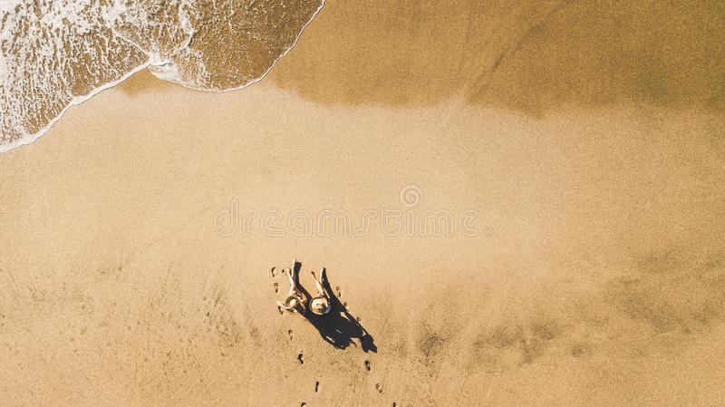 People enjoying vacation at the beach in resort hotel viewed  from vertical aerial pov - couple of girls sit down on the sand for royalty free stock photos