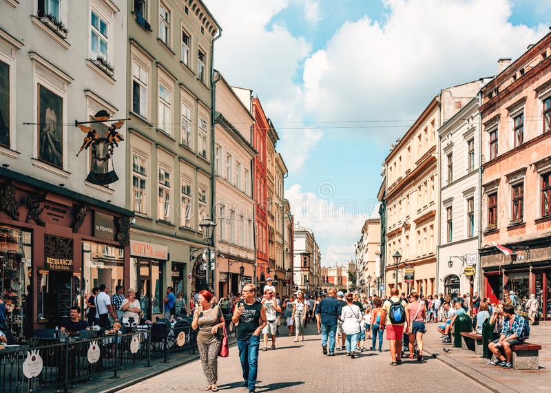 Couples and young families with children walking on busy street in old town Krakow. People enjoying warm summer Sunday by walking, eating ice creams and stock images
