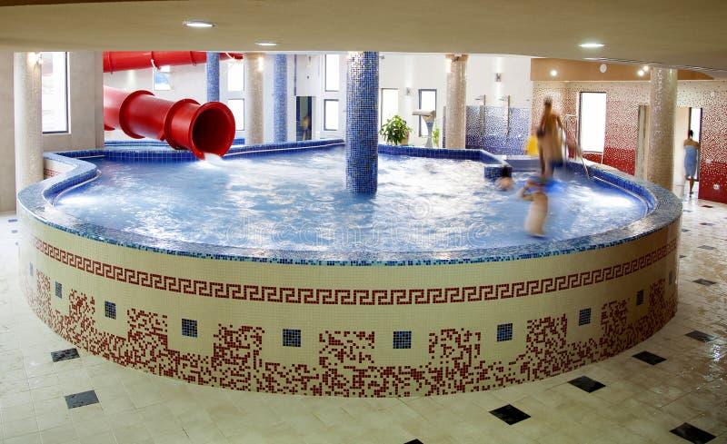 People enjoying water slide at pool. People enjoying water slide at inside pool, spa center, water park royalty free stock photography