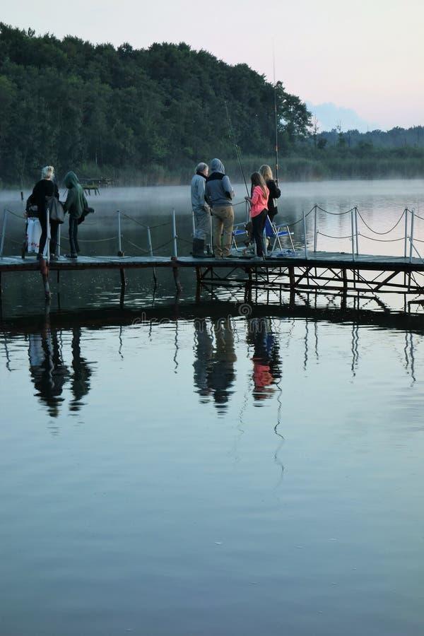 People enjoyinga chilly quiet evening at a lake stock image