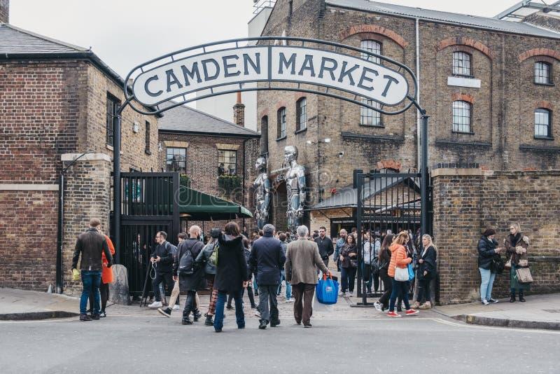 People entering Camden Market, London, UK, through the gates, under a name sign stock image