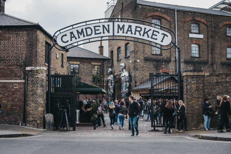 People entering Camden Market, London, UK, through the gates, under a name sign royalty free stock photos