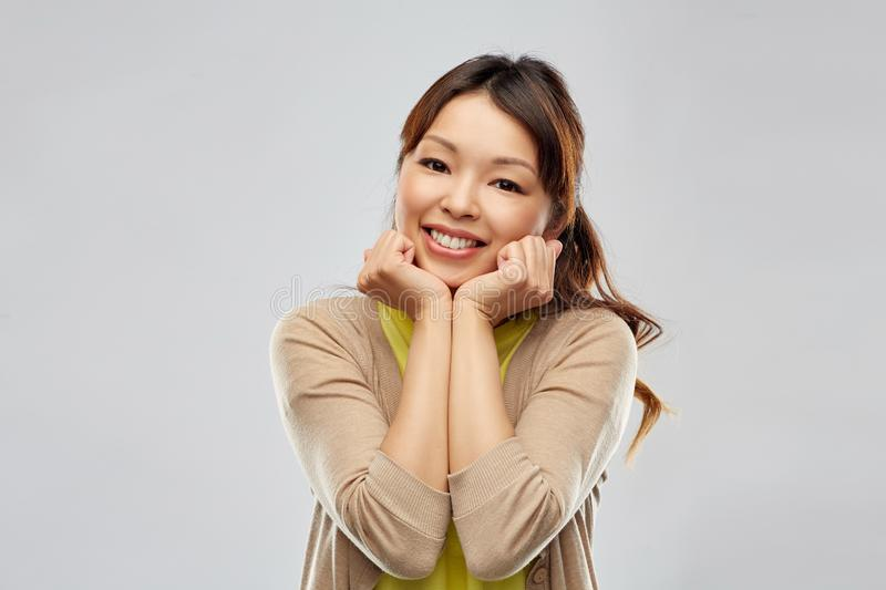 Cute asian woman over grey background stock photography