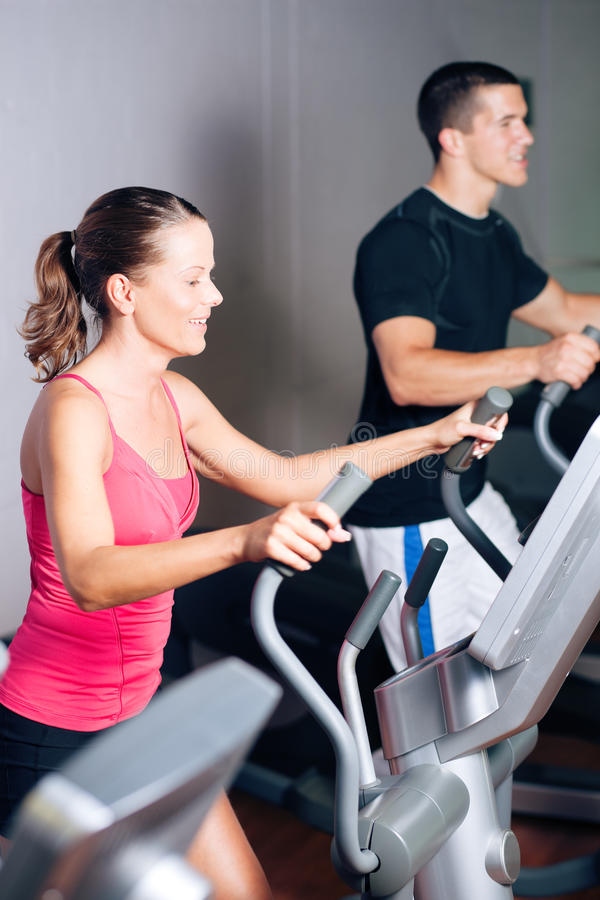 People exercising on elliptical trainer in gym stock photo