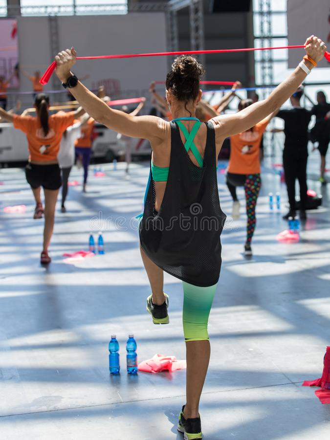 People Exercising with Fitness Elastic Band in Class at Gym with Music and Teacher on Stage.  royalty free stock photo