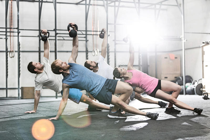 People exercising with kettlebells at crossfit gym stock image