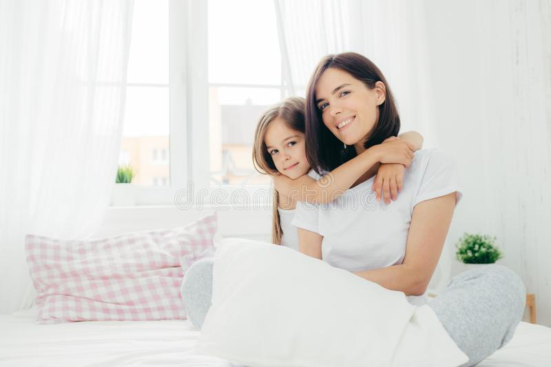 People, family and bedding concept. Cheerful young smiling mother and her daughter embrace each other, have positive expression, w royalty free stock image