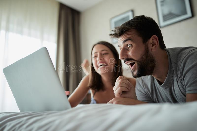 People, family, bedtime and fun concept -Couple with laptop in bed surfing on the net at laptop. People, family, bedtime and fun concept -Young couple with royalty free stock image