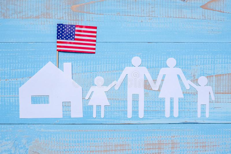 People or Family and home paper shape with  flag of the United States of America on blue wooden background. USA holiday of stock photos