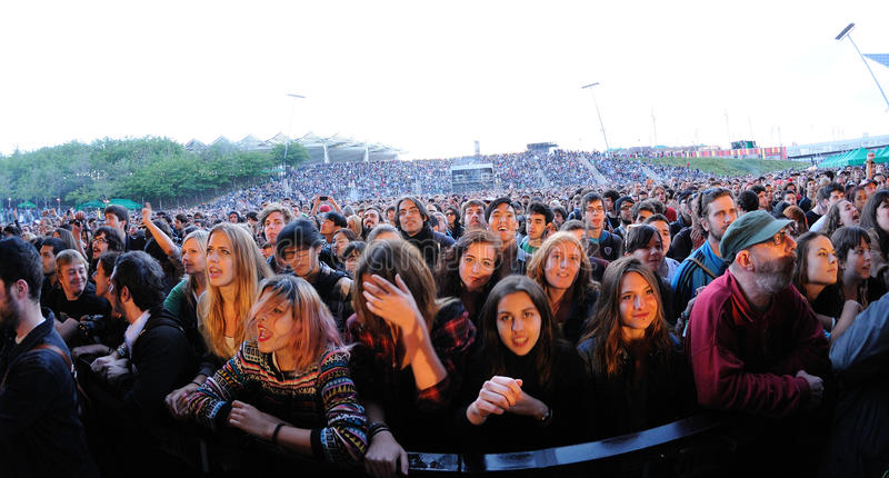 People (fans) scream and dance in the first row of a concert at Heineken Primavera Sound 2013 Festival stock image