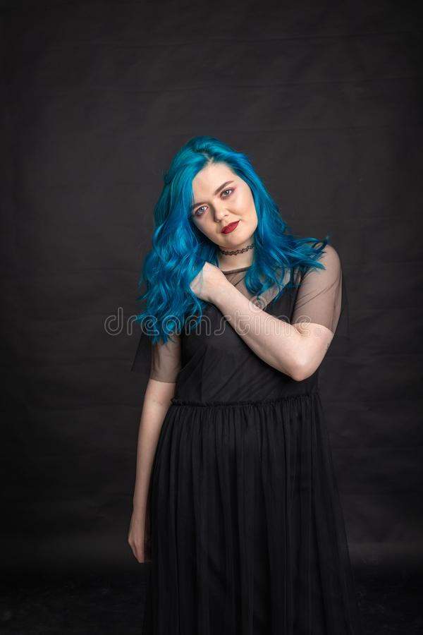 People and fashion concept - Woman with blue long hair dressed in black dress posing over black background stock image