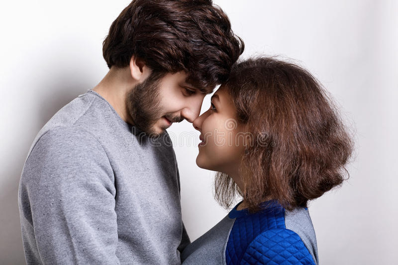 People, feelings, relations concept. Portrait of happy beautiful couple: young bearded guy and attractive girl touching each other stock images
