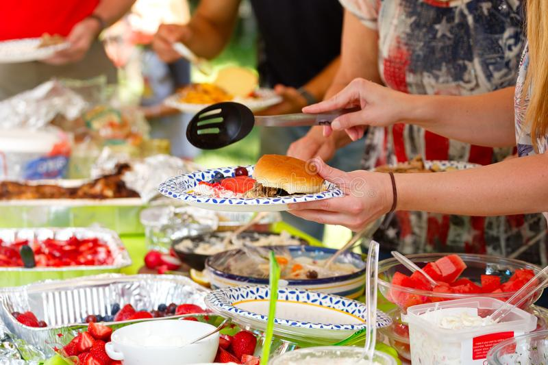 People at a Summer Potluck Picnic. People filling plates from a variety of food choices at a summer potluck gathering stock photos