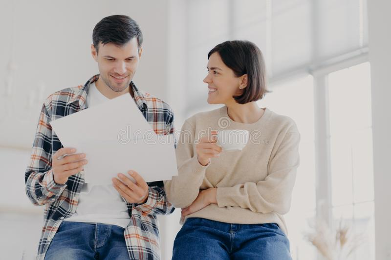 People, finances and collaboation concept. Happy European family couple analyze documents or contract terms, work with stock photos