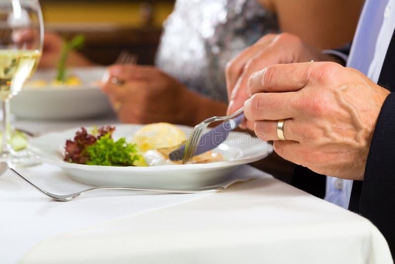 People fine dining in elegant restaurant. People fine dining food at table in hotel or elegant restaurant royalty free stock photos