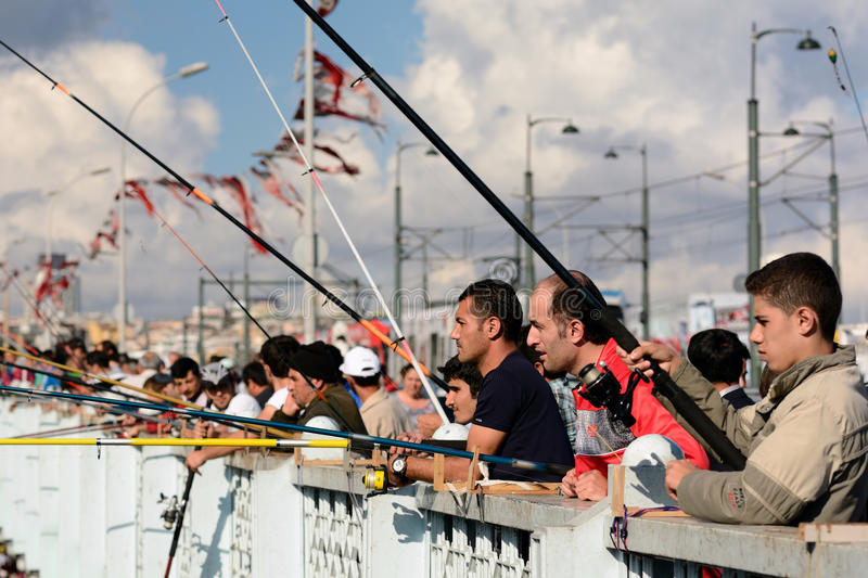 People fishing on the Galata Bridge in Istanbul, Turkey. A group of people fishing and socializing on the Galata Bridge that crosses the Golden Horn in Istanbul stock images