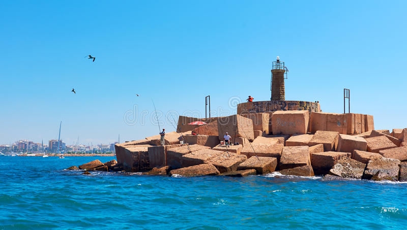 People with fishing rods on the lighthouse of Torrevieja. Spain stock photography