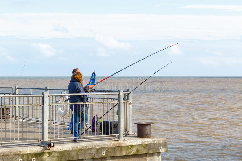 People fishing with fishing rods on Southwold Pier in the UK royalty free stock photos