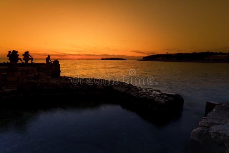 People fishing at sunset royalty free stock image