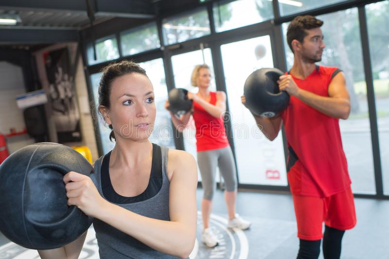 People in fitness class holding round prop stock images