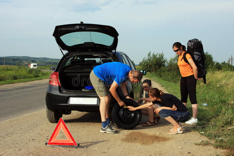 People fixing a flat tire. Young people thinking on the side of the road how to fix a flat tire royalty free stock photo