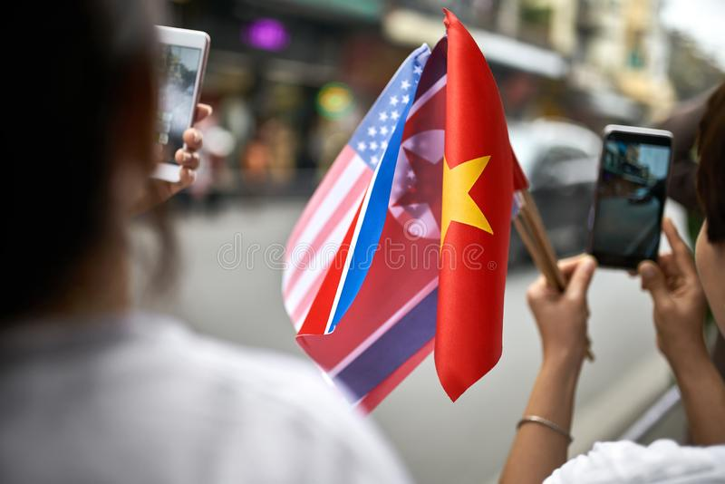 People with flags taking photos of diplomatic escort car passage. Two women are holding flags of the USA and Vietnam while taking photos on their cellphones royalty free stock photo